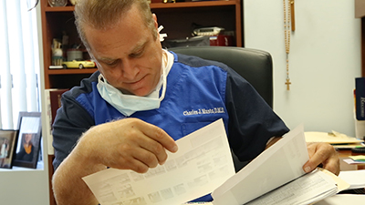 Dr. Musto looking over a referral form at Dr. Musto Periodontics & Dental Implants
